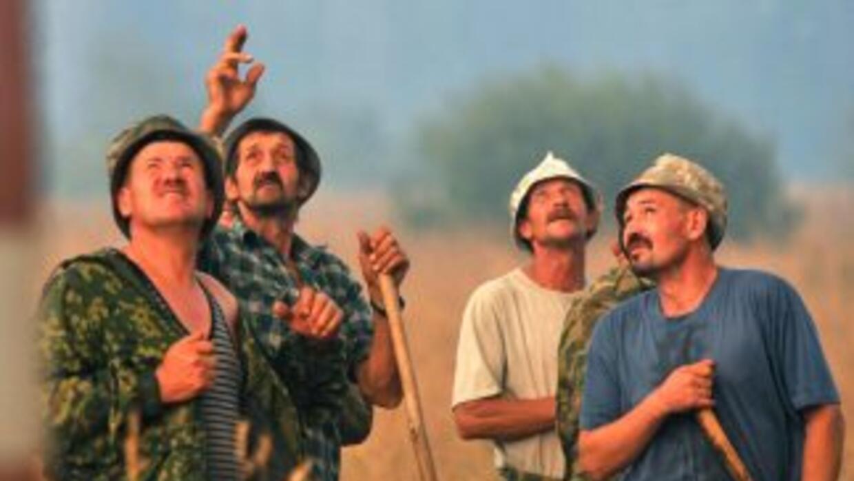 Trabajadores observan cómo se opropaga un incendio en un bosque de una r...