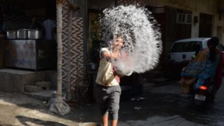 Un trabajador en India lanza agua sobre el pavimento, afuera de un resta...