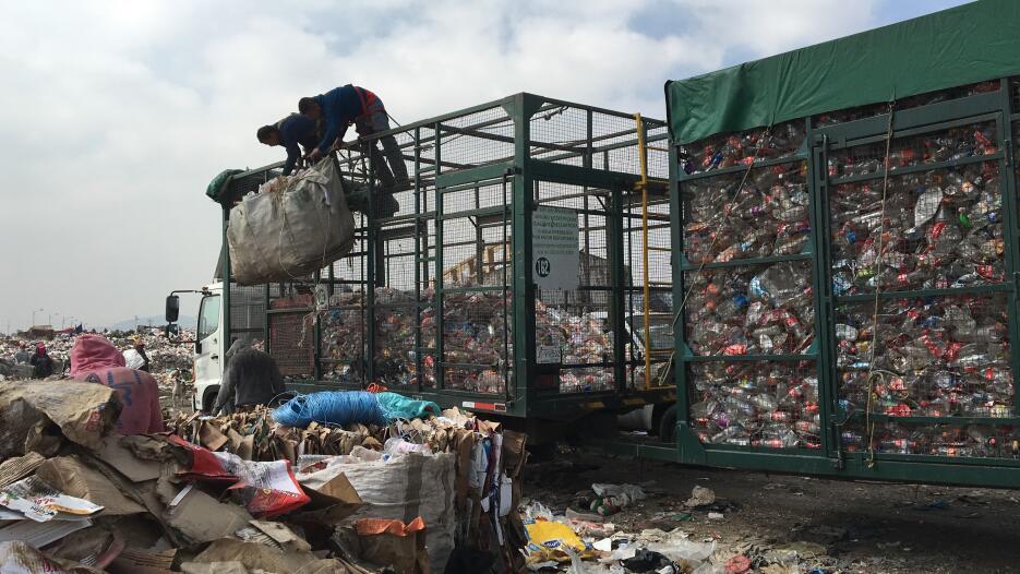 Empleados de Petstar cargan una bolsa con botellas plásticas usadas, que...