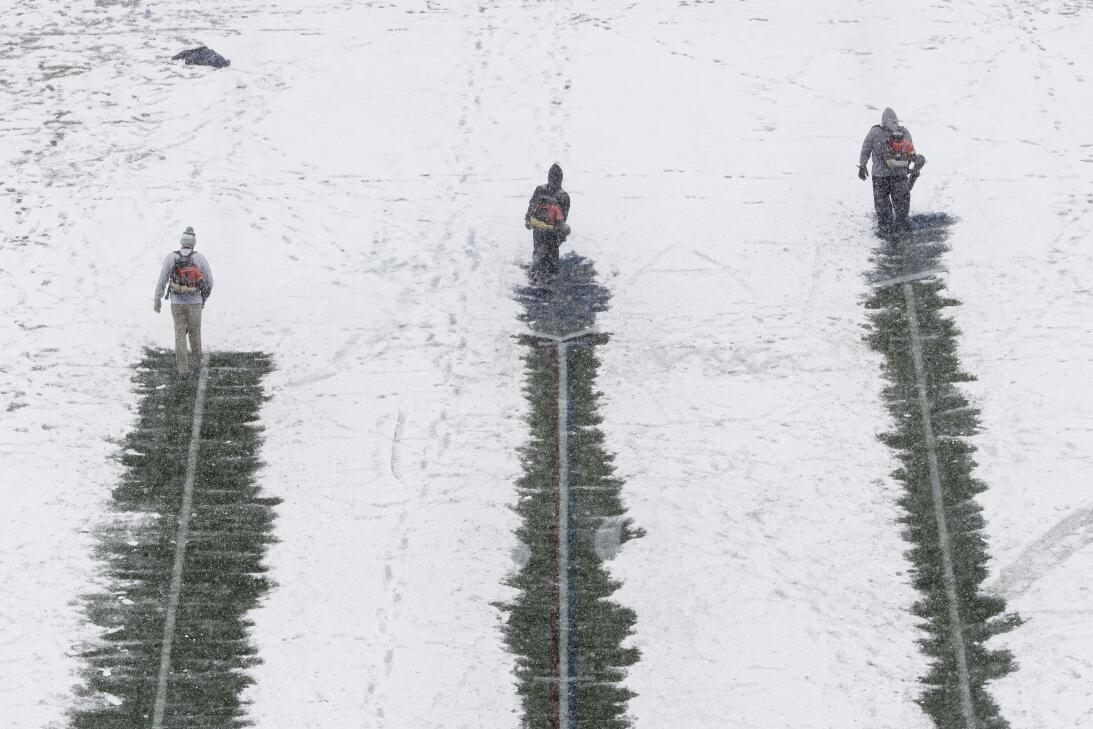 Members of the grounds crew clear lines on the field as snow falls ahead...