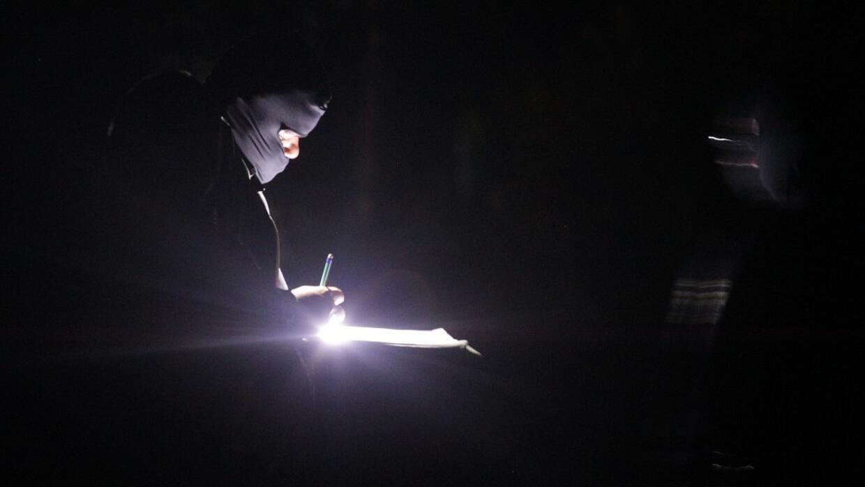 Un hombre con un pasamontañas ilumina un papel con una linterna.