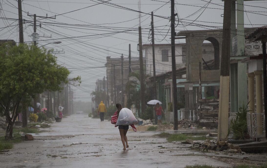 Residentes caminan bajo la lluvia en Caibarien, Cuba.