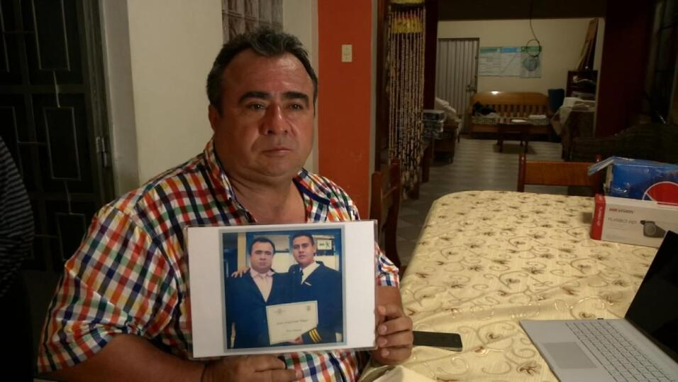 Néstor Clavijo shows a photo with his son disappeared in the Peruvian ju...