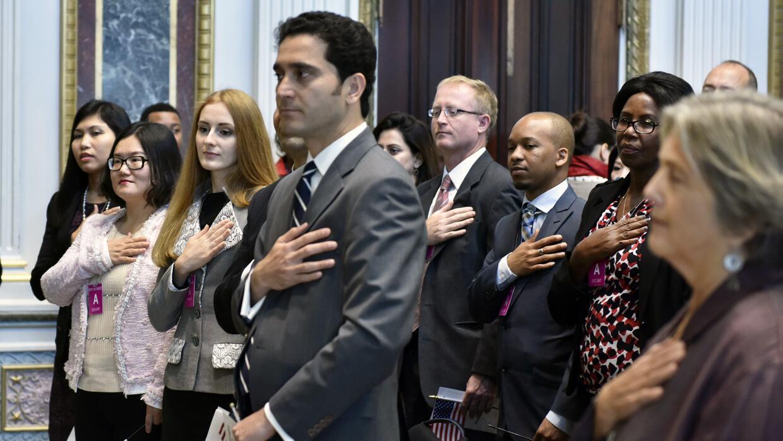 Los 15 nuevos ciudadanos prestan el juramento de rigor en la Casa Blanca.