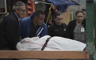 Médicos forenses retiran el cadáver de un individuo asesin...