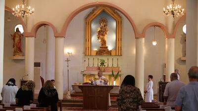Un sacerdote lidera una oración con cristianos iraquíes en una iglesia d...