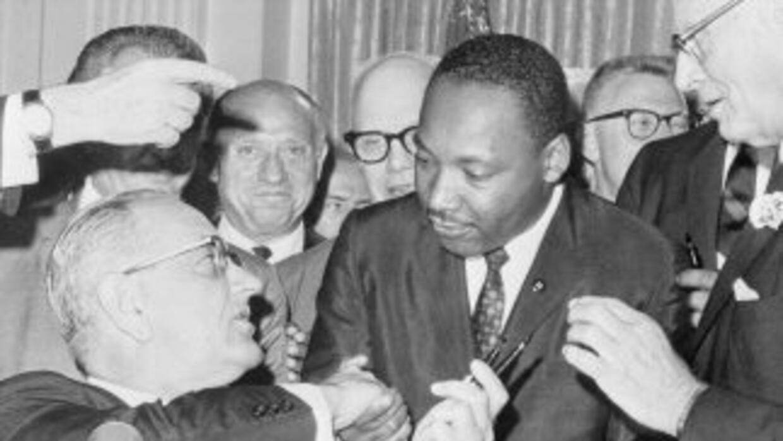 El presidente Lyndon Johnson estrecha la mano del clérigo y líder de los...