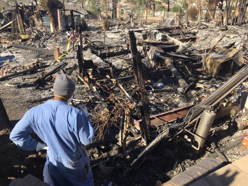 Un hombre observa una vivienda destruida por el fuego Creek en el barrio...