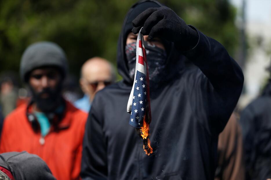 Una persona quema una bandera en protesta por las políticas del presiden...