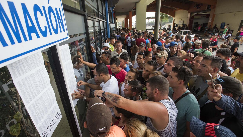 Un grupo de cubanos busca información en las primeras listas de cubanos...