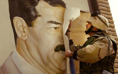 Un marine destroza un afiche del todavía presidente de Irak Sadda...