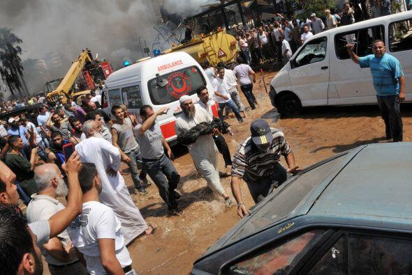 Un hombre libanés lleva el cuerpo quemado de una de las víctimas de la e...