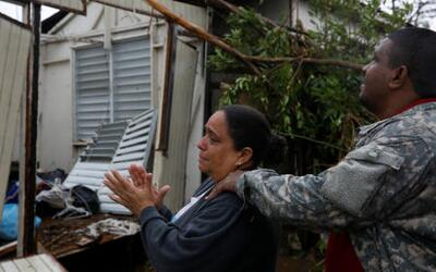 A family looks at the remains of their destroyed home in Guayama, Puerto...