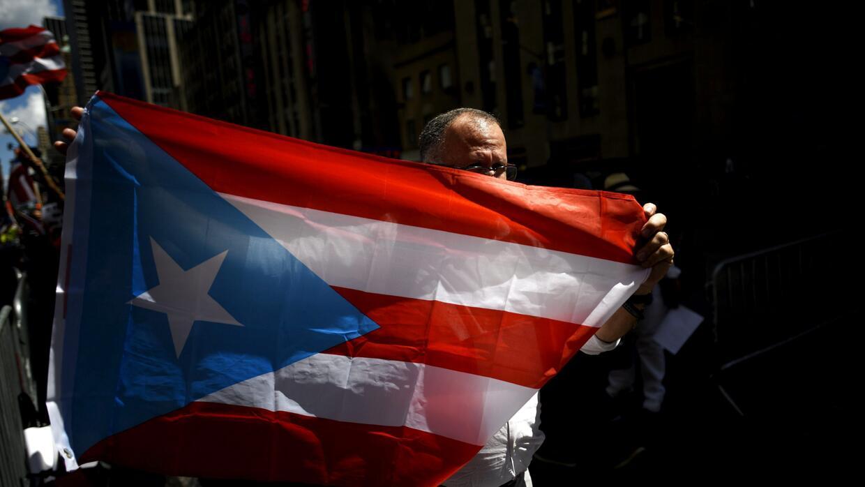 Un hombre sujeta una bandera de Puerto Rico durante una manifestación fr...