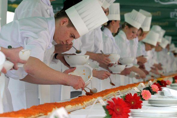 Los cocineros ponen caviar rojo en un intento de hacer el bocadillo m&aa...