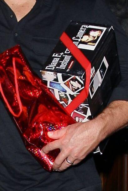 Y miren lo que llevaba bajo el brazo: una cámara de fotos polaroi...