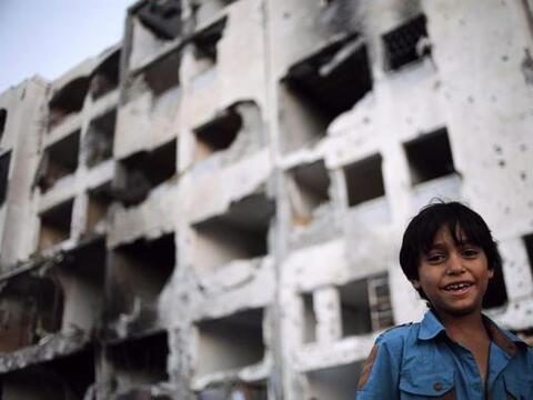 Un niño palestino sonríe mientras permanece cerca a un edi...