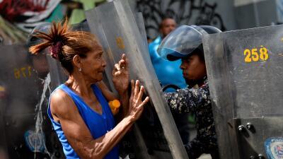 Una mujer en una protesta por falta de alimentos se enfrenta a fuerzas d...
