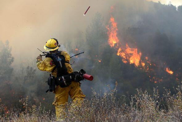 Un bombero lanza una bengala durante una operación.