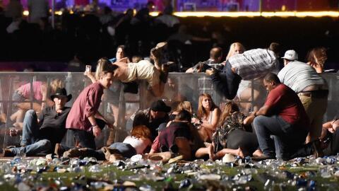 Asistentes al concierto tratan de protegerse de los disparos del atacante.