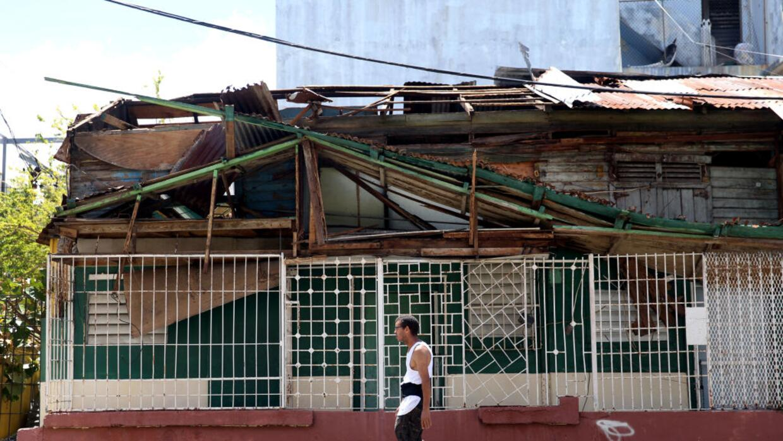Un hombre camina frente a una casa afectada por el huracán en San Juan,...