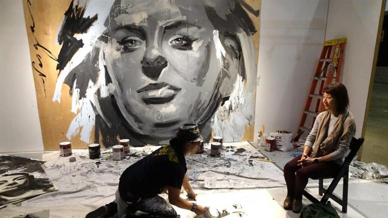 El artista trabaja en un retrato de una mujer.