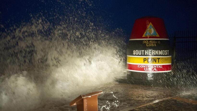 Waves smash into the marker at Key West's Southernmost Point of the...