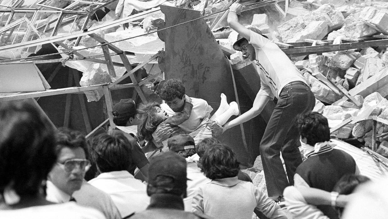 Un rescatista saca a un menor herido de un edificio derrumbado por el te...