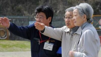 El emperador japonés Akihito y la emperatriz Michiko recorren un área de...
