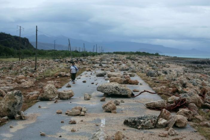 A woman walks on a highway blocked by rocks after the passage of hurrica...