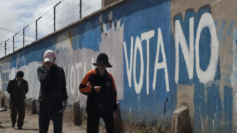 Bolivianos caminan junto a una pinta con referencia a la consulta