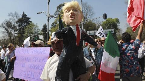 Un hombre carga una piñata con la figura del presidente Donald Tr...