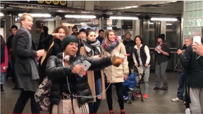 Subway riders stop in the middle of the terminal to sing and dance along...