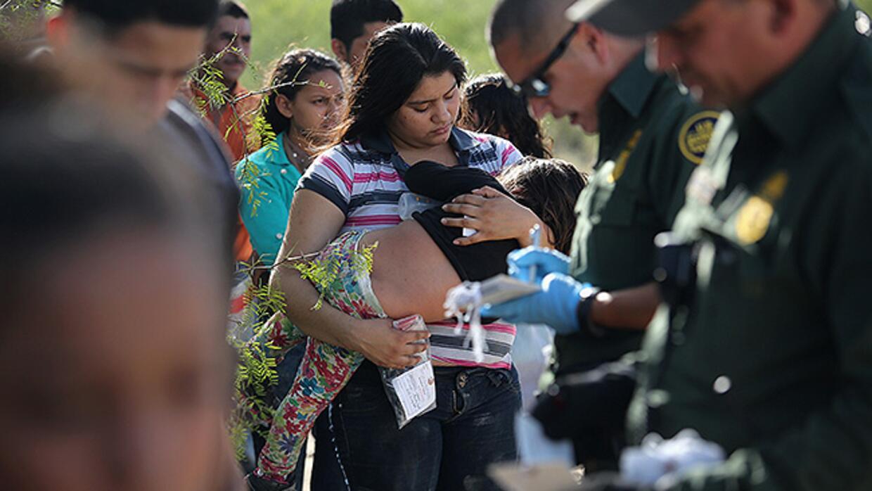 Un grupo de madres con hijos en brazos es detenida por agentes federales...