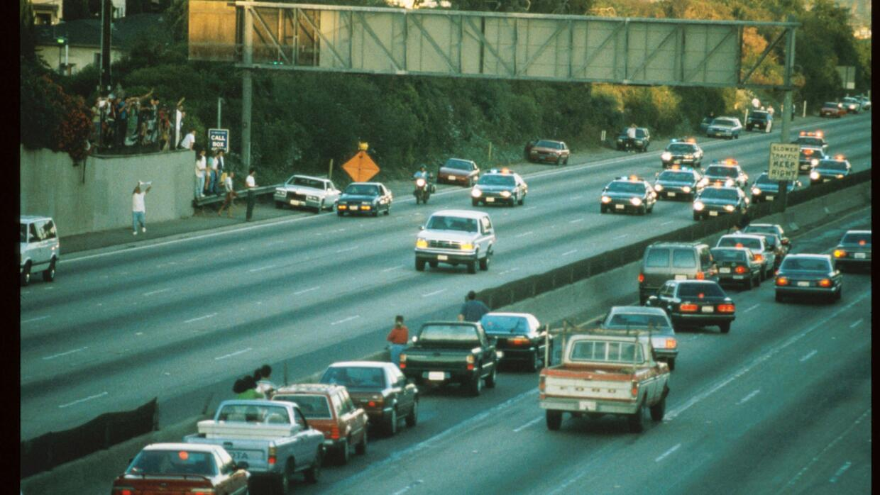 Police cars pursue a white, Ford Bronco down the highway in Los Angeles,...
