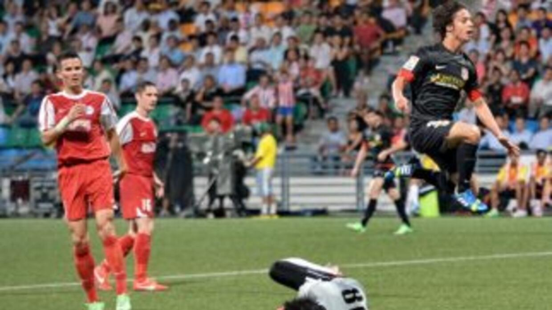 Oliver Torres, del Atlético de Madrid, salta sobre el portero de Singapur.