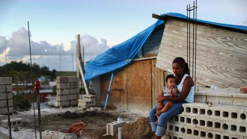 Isamar abraza a su hijo, Saniel, afuera de su casa en San Isidro, Puerto...