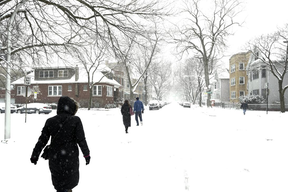 Vecinos caminan sobre la nieve en las calles del barrio Lakeview, en Chi...