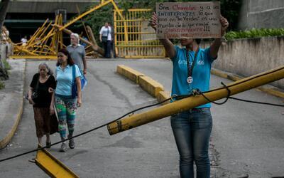 Una mujer protesta en la entrada de las residencias Los Verdes ubicadas...