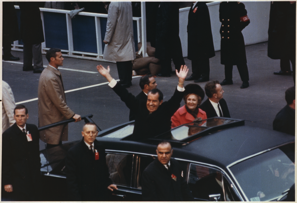President_and_Mrs._Nixon_waving_to_the_crowd_from_the_Presidential_limou...
