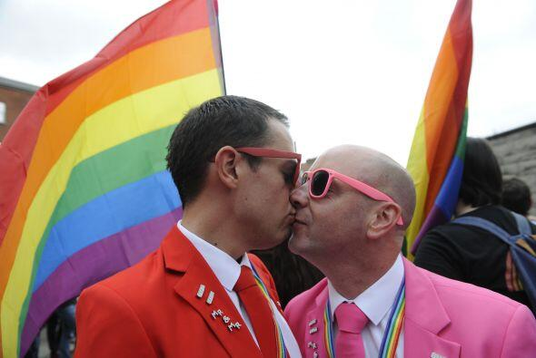 Dos hombres se besan en Dublín con la bandera del orgullo gay como fondo.