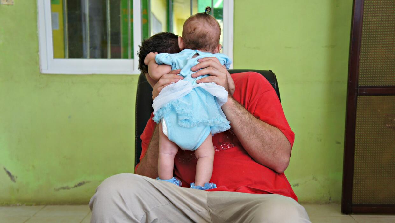 David, un carpintero de El Salvador, juega con su hija en Tapachula, Mex...
