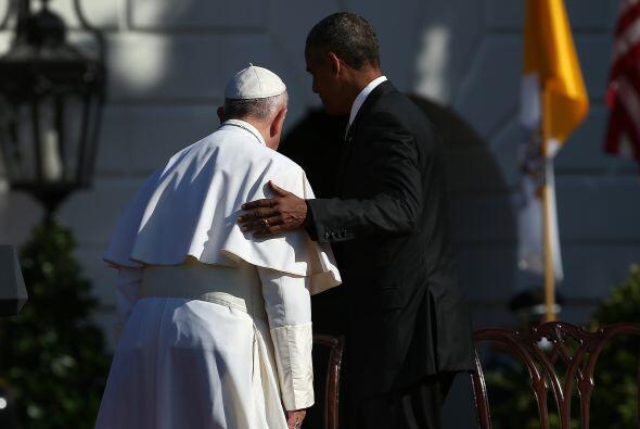 Como a un amigo, Obama toma a Francisco de su brazo derecho, al final de...