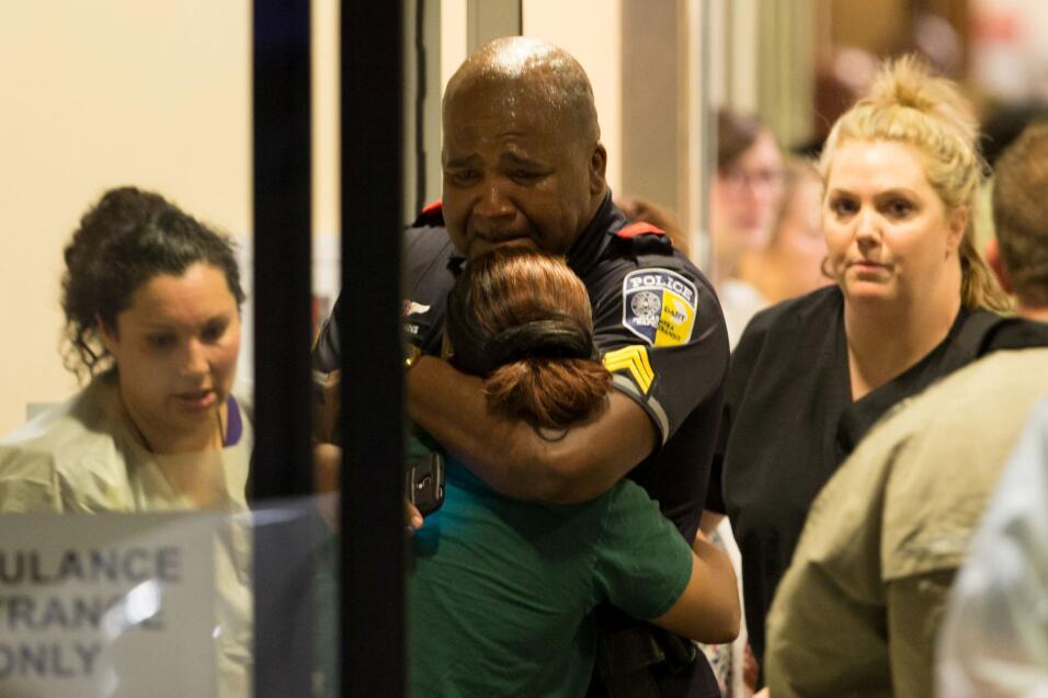 Un policía de tránsito de Dallas es consolado en la entrada de emergenci...