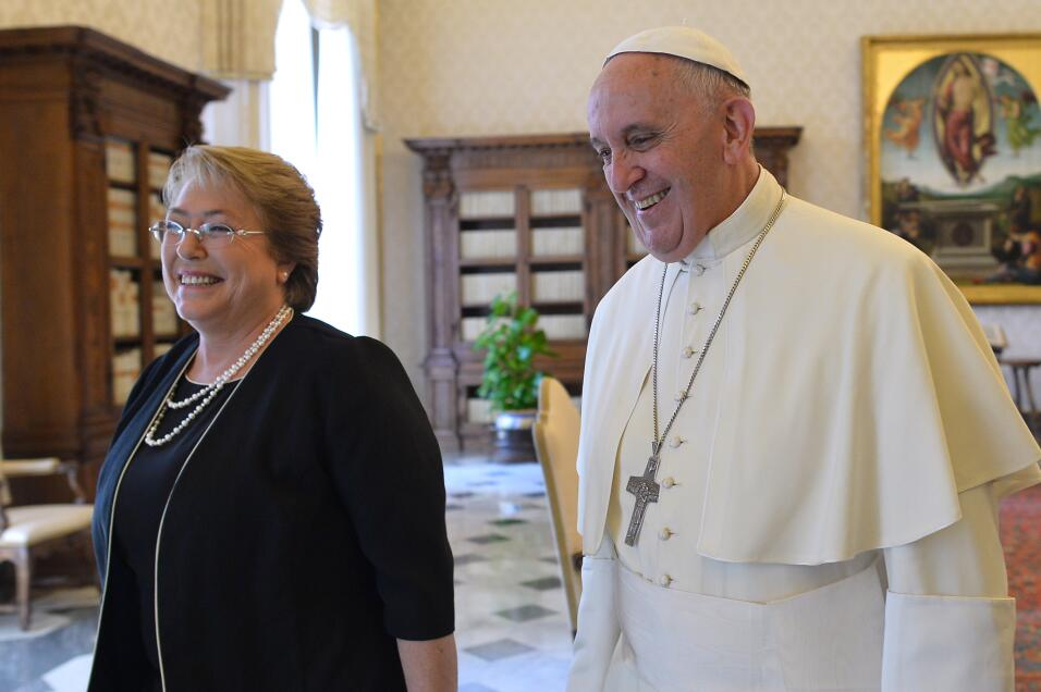 Pope Francis walks along with Chile's President Michelle Bachelet af...