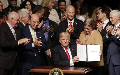 El presidente Donald Trump muestra la orden ejecutiva firmada en Miami p...