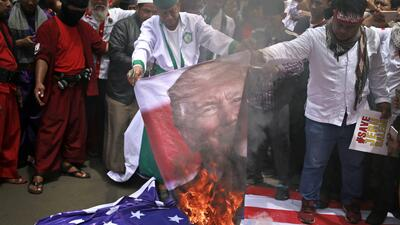 Manifestantes queman un cartel con la imagen del presidente de Estados U...