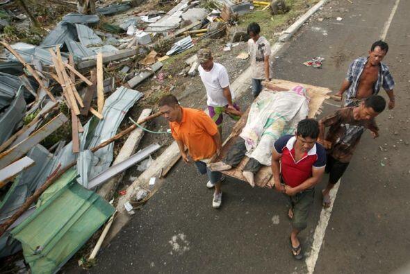 Filipinos cargan una victima del supertifón Haiyan en la devastada ciuda...