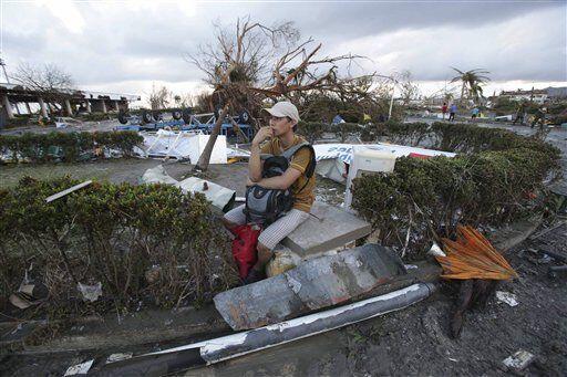 Un hombre se sienta entre los escombros con un árbol caído al fondo, trá...