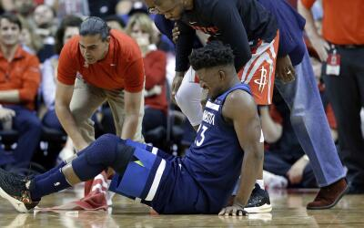 Jimmy Butler de los Minnesota Timberwolves reacciona a una lesión...